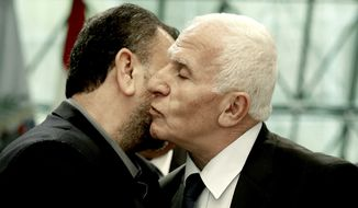Senior Fatah official Azzam al-Ahmad (right) and Hamas' representative, Saleh al-Arouri, kissed after signing a reconciliation deal Thursday in Cairo. (Associated Press)