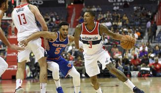 Washington Wizards guard Bradley Beal (3) dribbles against New York Knicks guard Courtney Lee (5) during the second half of a preseason NBA basketball game, Friday, Oct. 6, 2017, in Washington. Also seen is Wizards center Marcin Gortat (13), of Poland. The Wizards won 104-100. (AP Photo/Nick Wass)