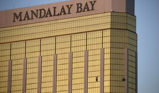 In this Monday, Oct. 2, 2017 file photo, drapes billow out of broken windows at the Mandalay Bay resort and casino on the Las Vegas Strip, following a deadly shooting at a music festival in Las Vegas. (AP Photo/John Locher, File)