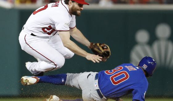 Washington Nationals second baseman Daniel Murphy (20) jumps after forcing out Chicago Cub's Jon Jay (30) on a ball hit by Kris Bryant, who was safe at first during seventh the inning of Game 5 of a baseball National League Division Series, at Nationals Park, Thursday, Oct. 12, 2017, in Washington. Kyle Schwarber scored on the play. (AP Photo/Alex Brandon)