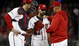 Washington Nationals starting pitcher Gio Gonzalez, center talks to pitching coach Mike Maddux as catch Matt Wieters listens during the third inning in Game 5 of baseball's National League Division Series against the Chicago Cubs, at Nationals Park, Thursday, Oct. 12, 2017, in Washington.  (AP Photo/Alex Brandon)