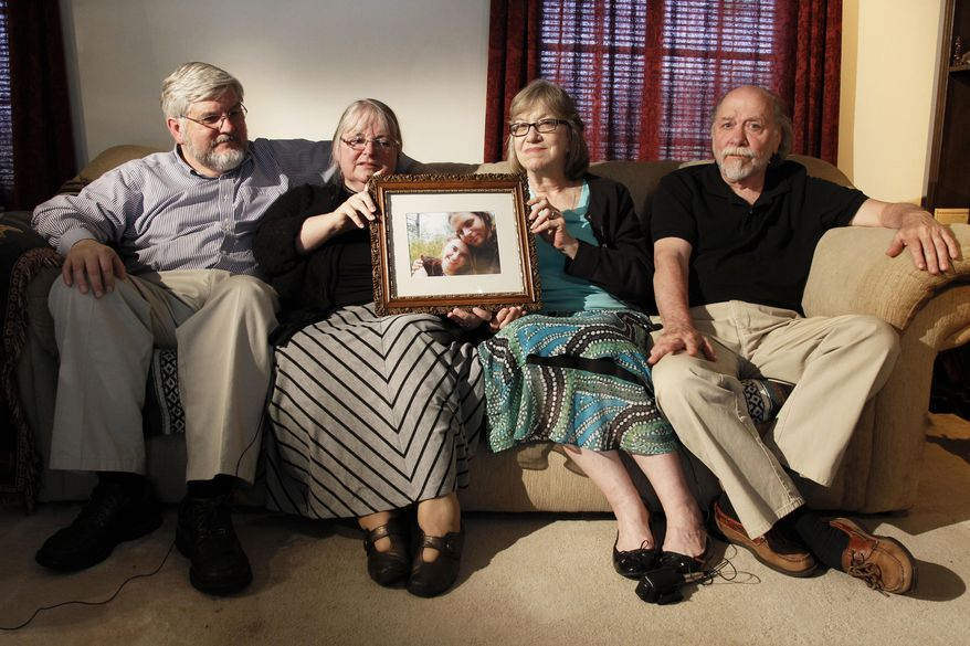 In this June 4, 2014, file photo, from left, Patrick Boyle, Linda Boyle, Lyn Coleman and Jim Coleman hold photo of their kidnapped children, Joshua Boyle and Caitlan Coleman, who were kidnapped by the Taliban in late 2012, Wednesday, June 4, 2014, in Stewartstown, Pa.  Pakistan's military says soldiers have recovered five Western hostages held by the Taliban for years. Pakistan's army did not name those held, only saying it worked with U.S. intelligence officials to track down the hostages and free them after discovering they had been brought into Pakistan.  (AP Photo/Bill Gorman, File)