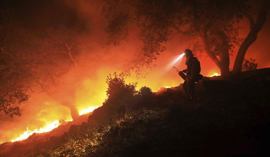 A San Diego Cal Fire firefighter monitors a flare up on a the head of a wildfire (the Southern LNU Complex), off of High Road above the Sonoma Valley, Wednesday Oct. 11, 2017, in Sonoma, Calif. A wind shift caused flames to move quickly up hill and threaten homes in the area. Three days after the fires began, firefighters were still unable to gain control of the blazes that had turned entire Northern California neighborhoods to ash and destroyed thousands of homes and businesses.  (Kent Porter/The Press Democrat via AP)