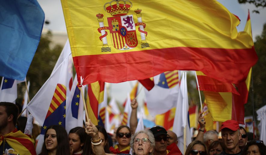 """A woman waves a Spanish flag while celebrating a holiday known as """"Dia de la Hispanidad"""" or Spain's National Day in Barcelona, Spain, Thursday, Oct. 12, 2017. Spain's celebrates its national day amid one of the country's biggest crises ever as its powerful northeastern region of Catalonia threatens independence. (AP Photo/Manu Fernandez)"""