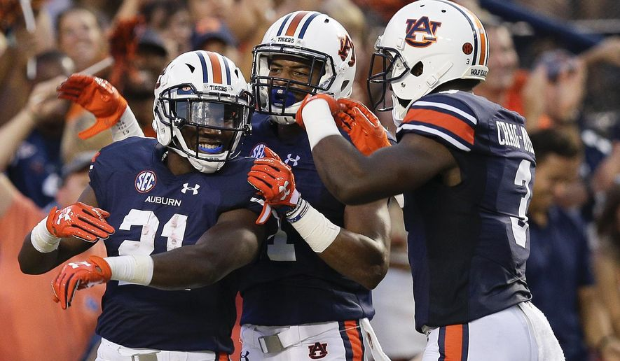FILE - In this Sept. 2, 2017, file photo, Auburn running back Kerryon Johnson, left, wide receiver Darius Slayton, center, and wide receiver Nate Craig-Myers, right, celebrates Johnson's touchdown in the first half of an NCAA college football game against Georgia Southern, in Auburn, Ala. Overshadowed entering the season by teammate Kamryn Pettway and other SEC runners, Johnson has delivered three straight huge performances for the Tigers leading up to Saturday's game at LSU.(AP Photo/Brynn Anderson, File)