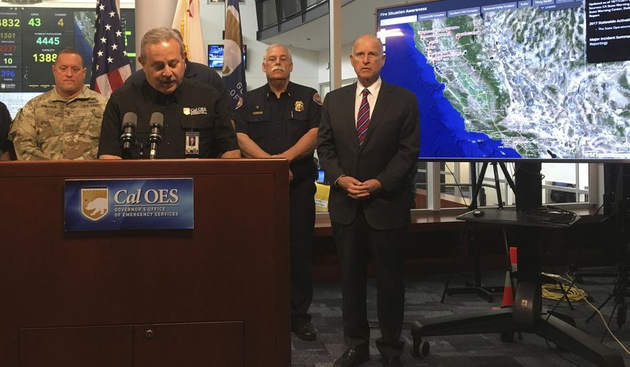 California Gov. Jerry Brown, far right, waits to speak after Mark Ghilarducci, at podium, director of the Governor's Office of Emergency Services, during a media briefing on California wildfires, at Cal OES headquarters near Sacramento, Wednesday, Oct. 11, 2017.  Gov. Brown warned that catastrophic wildfires will keep ripping through the state as the climate warms.  (AP Photo/Donald Thompson)