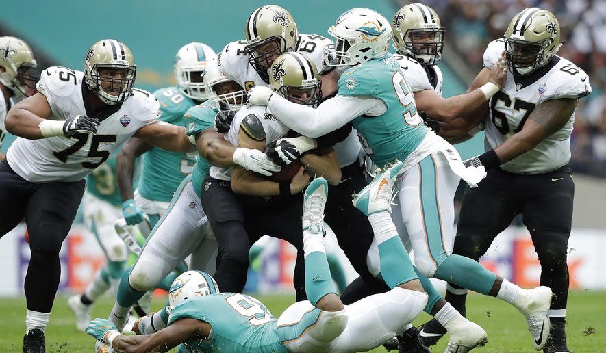 FILE - In this Oct. 1, 2017, file photo, New Orleans Saints quarterback Drew Brees, center, is sacked against the Miami Dolphins defense during the first half of an NFL football game at Wembley Stadium in London.  The Dolphins' offense ranks as the NFL's worst, and their defense is among the best, but players say there's no friction between the two units. (AP Photo/Matt Dunham, File)