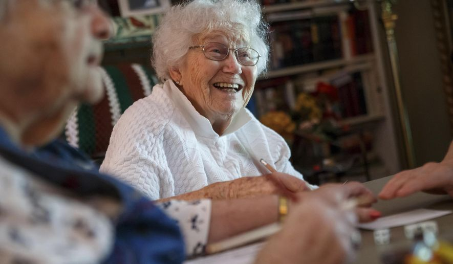 In this Sept. 12, 2017 photo, Garnette Winch, 91, smiles as the Bunco players at her table  debate scoring styles during the monthly Bunco game at the home of Betty Flynn on Winch Road in Springfield, Ill. The tradition of meeting once a month in various homes for the group to play Bunco goes back at least 70 years with families that have lived on Winch Road. The progressive dice game, under its original name of 8-Dice Cloth, was played in England during the 18th century, according to the World Bunco Association.(Justin L. Fowler/The State Journal-Register via AP)