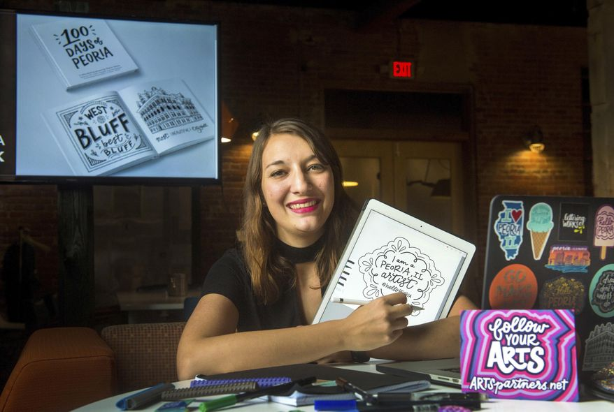 In this Aug. 28, 2017 photo, Chelsie Tamms is seen with some her hand lettering art work in  Peoria, Ill. Tamms is an artist who specializes in hand lettering for logo design, a craft rarely found in this rasterized era. A recent graduate of Bradley University, Chelsie has decided to set up her shop, Lettering Works, in the Peoria market. She has already created designs projects for the city, county and local area companies. (Fred Zwichy/Journal Star via AP)
