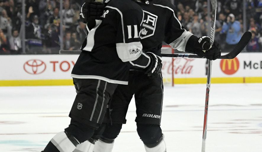 Los Angeles Kings center Anze Kopitar, left, of Slovenia, celebrates his goal with defenseman Christian Folin, of Sweden, during the second period of an NHL hockey game against the Calgary Flames, Wednesday, Oct. 11, 2017, in Los Angeles. (AP Photo/Mark J. Terrill)