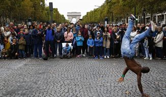 "FILE - In this Oct.1 2017 file photo, people watch a dancing performance on the champs Elysees avenue during the ""day without cars"", in Paris. In its latest initiative to reduce pollution, Paris City Hall is planning to ban gas-powered cars by 2030. The controversial move follows Mayor Anne Hidalgo's plan to ban all diesel cars from the city by 2024, when Paris will host the Summer Olympics.(AP Photo/Thiabult Camus, FILE)"