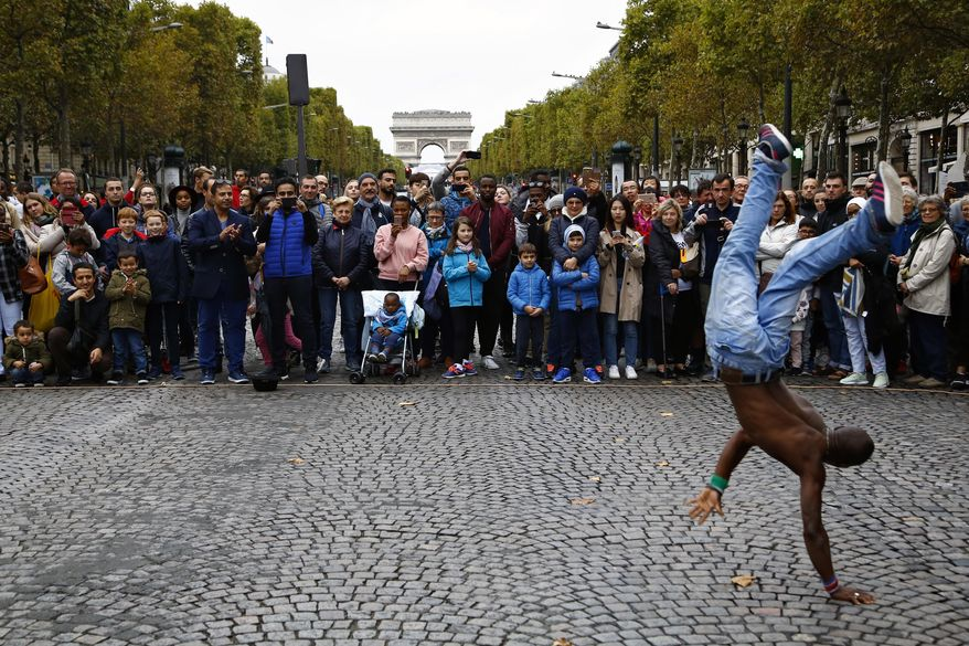 """FILE - In this Oct.1 2017 file photo, people watch a dancing performance on the champs Elysees avenue during the """"day without cars"""", in Paris. In its latest initiative to reduce pollution, Paris City Hall is planning to ban gas-powered cars by 2030. The controversial move follows Mayor Anne Hidalgo's plan to ban all diesel cars from the city by 2024, when Paris will host the Summer Olympics.(AP Photo/Thiabult Camus, FILE)"""