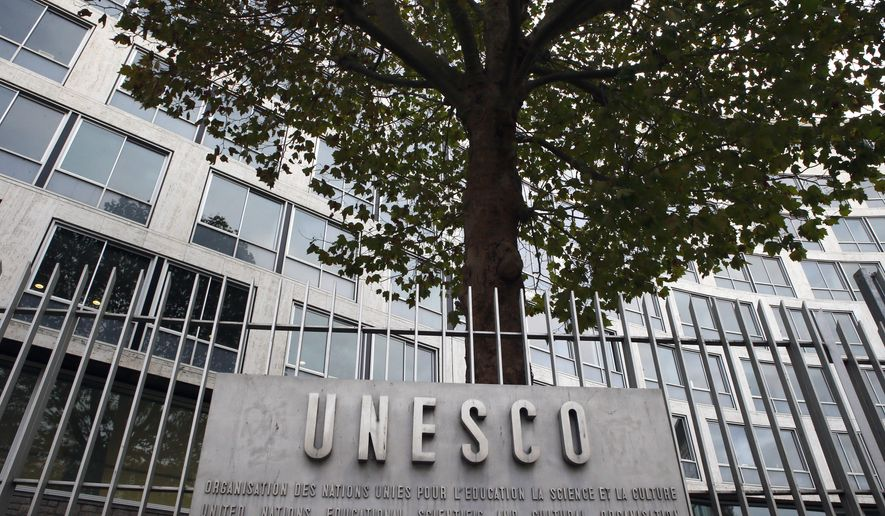 FILE - In this Monday Oct. 17, 2016 file picture, the United Nations Educational Scientific and Cultural Organization logo is pictured on the entrance at UNESCO's headquarters in Paris. U.S. officials have told The Associated Press that the United States is pulling out of UNESCO, after repeated criticism of resolutions by the U.N. cultural agency that Washington sees as anti-Israel. (AP Photo/Francois Mori, File)