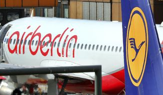 FILE - In the Sept. 21, 2017 file photo an Air Berlin plane sits behind a Lufthansa plane in Tegel airport in Berlin. (Wolfgang Kumm/dpa via AP)