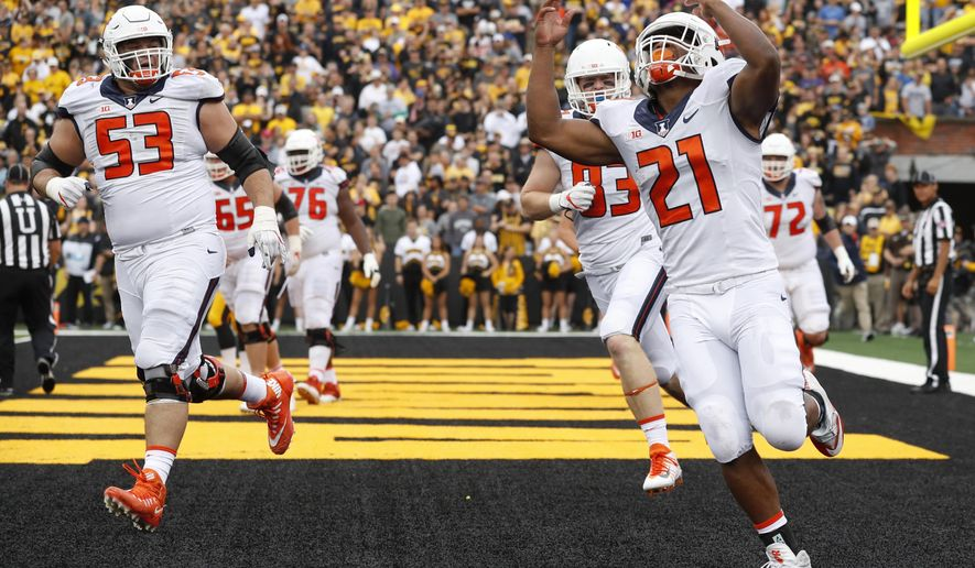 FILE - In this Oct. 7, 2017, file photo, Illinois running back Ra'Von Bonner (21) celebrates after scoring on a two-yard touchdown run during the first half of an NCAA college football game against Iowa in Iowa City, Iowa. Illinois piled up 200 rushing yards in a loss at Iowa last weekend, using primarily three running backs to do it. The Illini are hoping to ride the run to a win at home against Rutgers this Saturday.  (AP Photo/Charlie Neibergall, File)