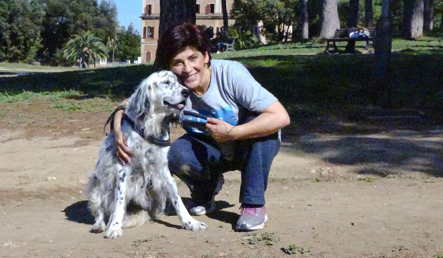 This undated photo made available Thursday, Oct. 12, 2017, shows an Italian librarian (name not available) who has won the right from her employer to use family sick leave to care for her ailing pet instead of having to use vacation days, posing with her dog Cucciola in a park in Rome. The woman said the dog is recovering well from surgery for a breast tumor and a larynx problem. The woman, who is single and has no family help for Cucciola, declined to be identified. (Str/ANSA via AP)
