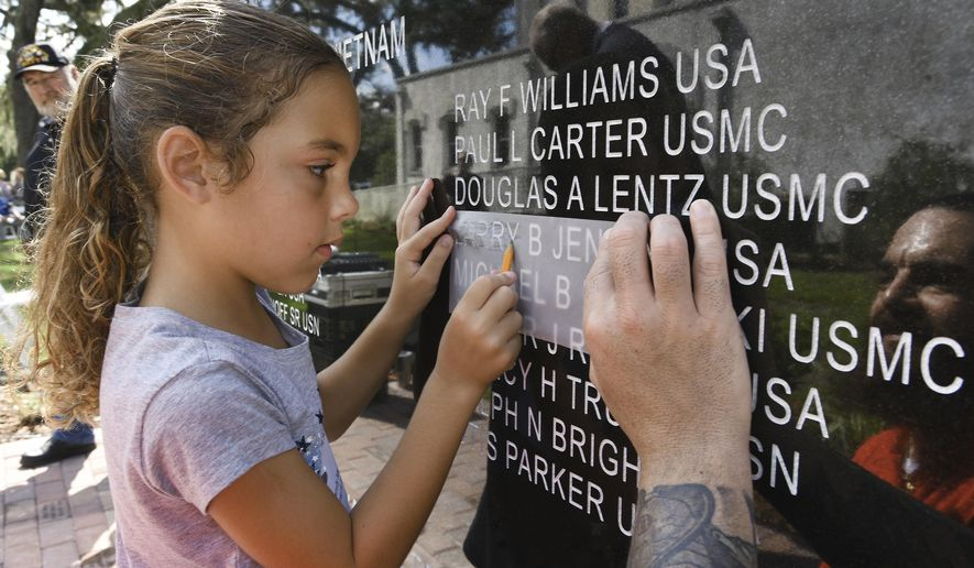 Angel Coyle, 7 of Fleming Island makes a rubbing of the name of Larry B. Jenkins with the help of her father Thomas Coyle after Monday's Taps Memorial dedication ceremony. Jenkins was Coyle's Great Uncle who was killed in Vietnam. Clay County residents gathered on the grounds of the old County Courthouse in Green Cove Springs, Fla., Monday, Oct. 9, 2017 to unveil the new Taps Memorial built to honor the county residents who have died during military service dating back to the Civil War.  (Bob Self/The Florida Times-Union via AP)