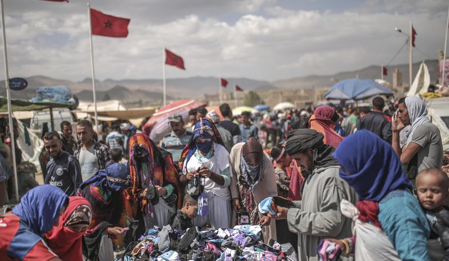 In this Friday, Sept. 22, 2017 photo, Berber villagers shop for garments at the annual festival of Imilchil, a small village in Morocco's Atlas mountains. What started as an annual marriage festival has become an economic boon for a tiny Berber village tucked into in the foothills of Morocco's Atlas Mountains. Today, the event is arranged to coincide with a large three-day market that marks the end of the harvest season. (AP Photo/Mosa'ab Elshamy)