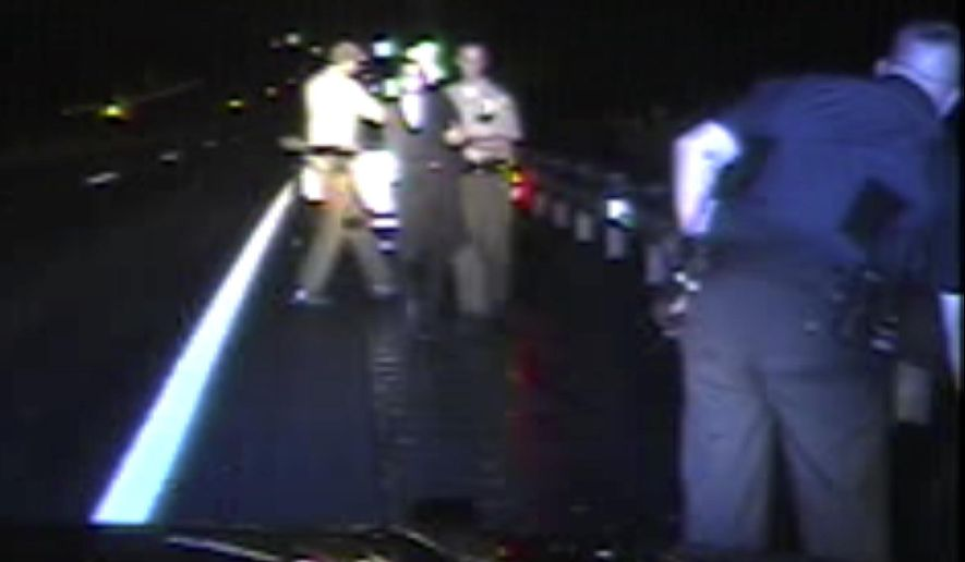 File - In this Aug. 8, 2017, file from dashboard video released by the Vermont State Police, troopers detain passenger Rabbi Eli Fink, rear, and driver Rabbi Berl Fink, off camera at right, during a traffic stop in Thetford, Vt. The attorney for the rabbi who drove for 4.5 miles after a Vermont state trooper tried to pull him over for speeding on a remote interstate highway says he's hopeful the case can be resolved without Fink having to appear in court. (Vermont State Police via AP, File)