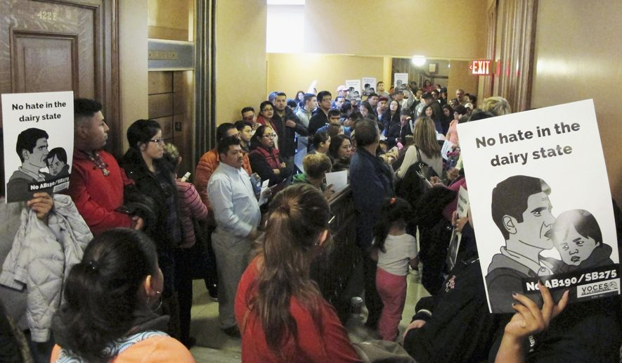 """A crowd of opponents to a bill in the Wisconsin Legislature that would outlaw """"sanctuary cities"""" fills the hallway outside of a hearing room Thursday, Oct. 12, 2017, in Madison, Wis. (AP Photo/Scott Bauer)"""