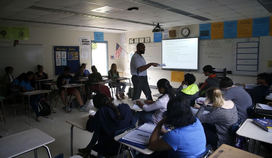 In this March 31, 2016 photo, students listen to their teacher during class at The LeRoy Collins Institute in Tallahassee, Fla.  The school is one of the five most highly-segregated school districts in the state. (Joe Rondone/Tallahassee Democrat via AP)