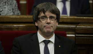 """Catalan regional President Carles Puigdemont waits to make his opening speech at the parliament in Barcelona, Spain, Tuesday, Oct. 10, 2017. Puigdemont says he has a mandate to declare independence for the northeastern region, but proposes waiting """"a few weeks"""" in order to facilitate a dialogue. (AP Photo/Manu Fernandez)"""