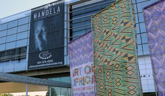 """In this Oct. 10, 2017 photo, fabric banners stand in front of the Clinton Presidential Center in Little Rock, Ark. The Clinton Library is presenting """"Mandela: The Journey to Ubuntu"""" and """"Art of Africa: One Continent, Limitless Vision"""" until February. (AP Photo/Kelly P. Kissel)"""