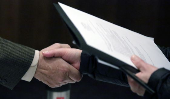 In this April 22, 2015, file photo, a recruiter, left, shakes hands with a job seeker during a National Career Fairs job fair in Chicago. (AP Photo/M. Spencer Green, File)
