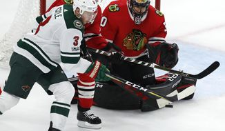 Chicago Blackhawks' Corey Crawford, right, makes a save on Minnesota Wild's Charlie Coyle during the second period of an NHL hockey game Thursday, Oct. 12, 2017, in Chicago. (AP Photo/Jim Young)