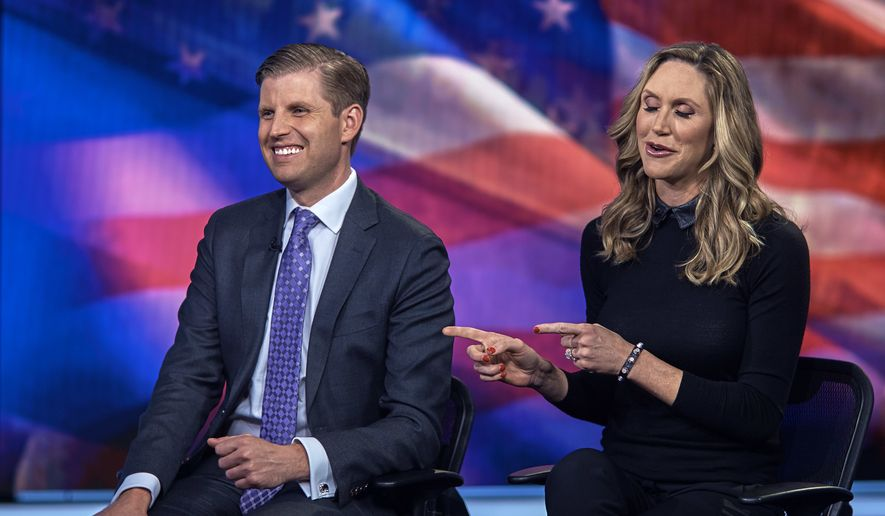 """Eric Trump, left, smiles and Lara Trump, right, talks as they tape a segment of """"Justice With Judge Jeanine,"""" at the Fox Studios in New York, Friday, Oct. 13, 2017. (AP Photo/Andres Kudacki)"""