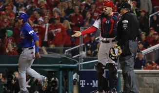 Washington Nationals catcher Matt Wieters (32) talks with umpire Jerry Lane as Chicago Cubs' Addison Russell, left, scores on a passed ball and throwing error by Wieters that allowed batter Javier Baez to reach second after striking out, during the firth inning in Game 5 of baseball's National League Division Series, at Nationals Park, Thursday, Oct. 12, 2017 in Washington. (AP Photo/Pablo Martinez Monsivais)