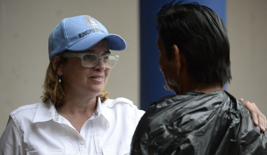In this Sept. 30, 2017, file photo San Juan, Puerto Rico, Mayor Carmen Yulin Cruz speaks with a man as she arrives at San Francisco hospital in the Rio Piedras area of the city as about 35 patients are evacuated after the failure of an electrical plant. The AP reported on Oct. 13, 2017, that a story claiming San Juan's city council has moved to impeach Cruz was false. (AP Photo/Carlos Giusti, File)