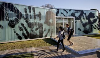 In this Friday, Oct. 6, 2017 photo, a man and woman walk by an installation created by Brazilian artist Regina Silveira as part of the South American biennale or Bienalsur, at Memory Park in Buenos Aires, Argentina. Bienalsur, now based in Buenos Aires, seeks to break the mold by bringing contemporary art to new audiences and allowing artists to experiment freely. (AP Photo/Victor R. Caivano)