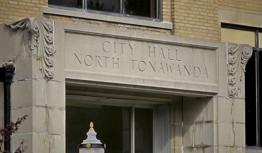 This photo shows signage above the entrance to North Tonawanda's City Hall where its city council resides, Thursday, Oct. 12, 2017, in New York. The council voted unanimously Oct. 3 to amend an existing law to add bullying, harassment and underage drinking to existing curfew violations parents already could be held accountable for. (AP Photo/Carolyn Thompson)