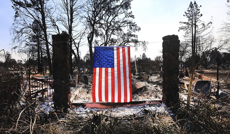 On Willowview Court in Santa Rosa, Calif., a homeowner displays an American flag amidst the destruction from a wildfire, Thursday Oct. 12, 2017. Since igniting Sunday in spots across eight counties, the fires have transformed many neighborhoods into wastelands. Thousands of homes and businesses have been destroyed and thousands of people were forced to flee. (Kent Porter/The Press Democrat via AP)