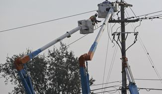 FILE - In this Wednesday, Oct. 11, 2017 file photo, a Pacific Gas and Electric crew works at restoring power along the Old Redwood Highway in Santa Rosa, Calif. Pacific Gas and Electric Co. shares plummeted 10.5 percent, after regulators directed the company to preserve any evidence of failed poles or other equipment that might be connected to Northern California wildfires that killed dozens of people. (AP Photo/Eric Risberg, File)
