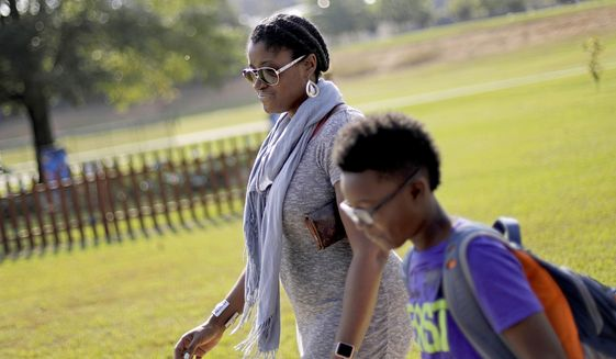 "Corrie Davis, left, picks up her son Turner from Big Shanty Elementary School in Kennesaw, Ga., Wednesday, Oct. 11, 2017. A new battle line has formed in the national debate over Civil War flags and symbols. The school last month invited fifth-graders to dress up as characters from the Civil War. Davis says a white student dressed as a plantation owner approached her son and said ""You are my slave."" Davis says she wants Cobb County school officials to understand the pain that caused her son. She also wants the school to stop the annual Civil War dress-up day. (AP Photo/David Goldman)"
