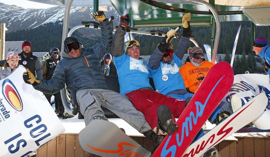 Snowboarders break through the banner to ride the first chair of the season during opening day at Arapahoe Basin Ski Area Friday, Oct. 13, 2017, in Colorado. A-Basin is the first ski resort in North America to open for the season. (AP Photo/Jack Dempsey)