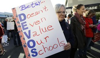 Colleen Webster, of Renton, Wash., holds a sign opposing U.S. Education Secretary Betsy DeVos, Friday, Oct. 13, 2017, outside the hotel where DeVos was scheduled to speak later in the evening in Bellevue, Wash. (AP Photo/Ted S. Warren)