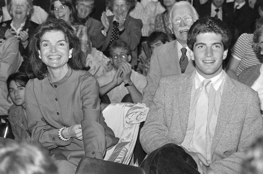 FILE - In this June 6, 1983 file photo, Jacqueline Kennedy Onassis, left, and her son John F. Kennedy Jr., wait to hear a speech by Sen. Edward Kennedy at Brown University in Providence, R.I. Brown University said Friday, Oct. 13, 2017, the college application of John F. Kennedy Jr. that is now up for auction was stolen, and it wants the documents back. The website MomentsInTime.com put an $85,000 price tag on a collection of documents, including Kennedy's application and letters from his mother discussing his time at Brown. (AP Photo/Peter Southwick, File)