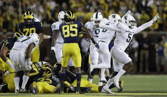 FILE - In this Oct. 7, 2017, file photo, Michigan State recovers a fumble from Michigan running back Ty Isaac during the first half of an NCAA college football game, in Ann Arbor, Mich. Michigan State's defense is back in prime form. That's a daunting matchup for a Minnesota offense that is lacking punch. (AP Photo/Carlos Osorio, File)