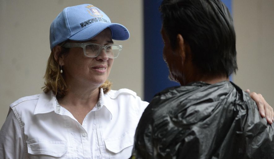 FILE - In this  Sept. 30, 2017, file photo San Juan, Puerto Rico, Mayor Carmen Yulin Cruz speaks with a man as she arrives at San Francisco hospital in the Rio Piedras area of the city as about 35 patients are evacuated after the failure of an electrical plant. The AP reported on Oct. 13, 2017, that a story claiming San Juan's city council has moved to impeach Cruz was false. (AP Photo/Carlos Giusti, File)