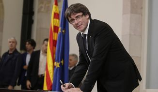 """Catalan regional President Carles Puigdemont signs an independence declaration document after a parliamentary session in Barcelona, Spain, Tuesday, Oct. 10, 2017. Puigdemont says he has a mandate to declare independence for the northeastern region, but proposes waiting """"a few weeks"""" in order to facilitate a dialogue. (AP Photo/Manu Fernandez)"""