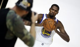 FILE - In this Sept. 22, 2017, file photo, Golden State Warriors' Kevin Durant poses for photos during the NBA basketball team's media day in Oakland , Calif. Beginning his 11th NBA season at age 29 and fresh off his first career championship, Durant is as determined as ever.  (AP Photo/Marcio Jose Sanchez, FIle)