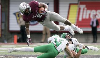 Montana running back Jeremy Calhoun (8) jumps over two North Dakota defenders in the first quarter of an NCAA college football game, Saturday, Oct. 14, 2017, in Missoula, Mont. (AP Photo/Patrick Record)