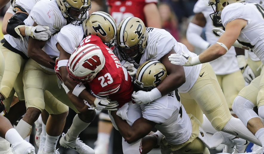 Wisconsin running back Jonathan Taylor is tackled by the Purdue defense during the first half of an NCAA college football game, Saturday, Oct. 14, 2017, in Madison, Wis. (AP Photo/Andy Manis)