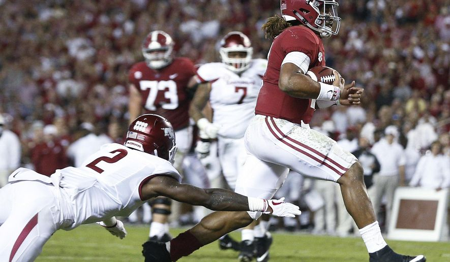 Alabama quarterback Jalen Hurts runs in for a touchdown as Arkansas defensive back Kamren Curl reaches for him during the first half an NCAA college football game Saturday, Oct. 14, 2017, in Tuscaloosa, Ala. (AP Photo/Brynn Anderson)