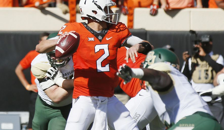 Oklahoma State quarterback Mason Rudolph (2) passes under pressure from Baylor's Brian Nance, right, in the second quarter of an NCAA college football game in Stillwater, Okla., Saturday, Oct. 14, 2017. (AP Photo/Sue Ogrocki)