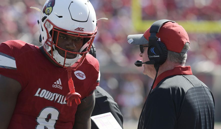 Louisville head coach Bobby Petrino, right, talks with quarterback Lamar Jackson (8) during the second half of an NCAA college football game against Boston College, Saturday, Oct. 14, 2017, in Louisville, Ky. Boston College won 45-42. (AP Photo/Timothy D. Easley)