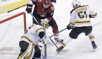 Boston Bruins goalie Anton Khudobin, left, makes a save on the shot by Arizona Coyotes' Lawson Crouse (67) as Boston Bruins' Ryan Spooner skates in to defend during the second period of an NHL hockey game, Saturday, Oct. 14, 2017, in Glendale, Ariz. (AP Photo/Ralph Freso)